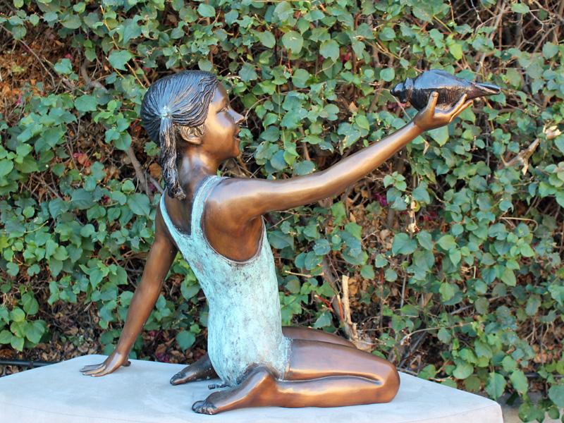 bronze statue of girl holding shell