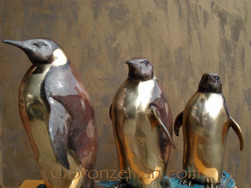 bronze statue of three penguins