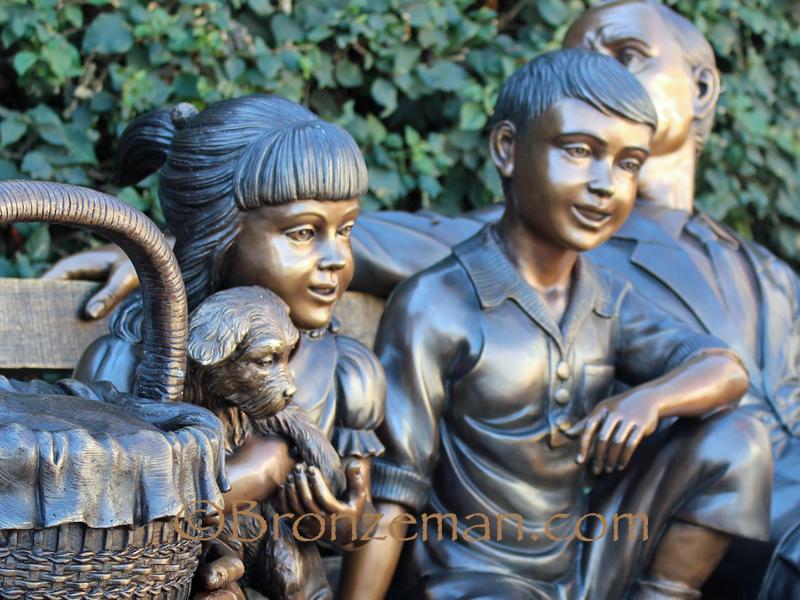 bronze sculpture of grandparents and children sitting on bench