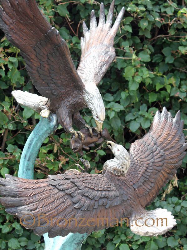 2 bronze eagles fighting over food