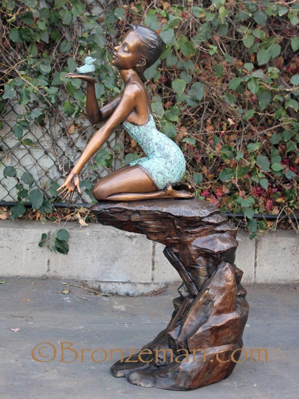 bronze sculpture of a girl with bird