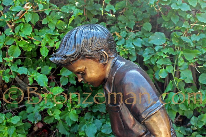 bronze statue of a boy golfing