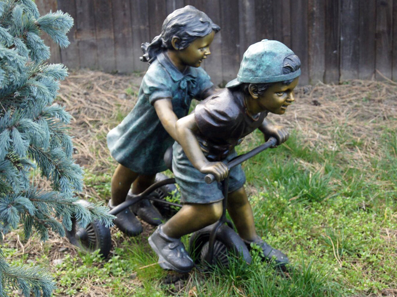 bronze boy and girl on tricycle statue