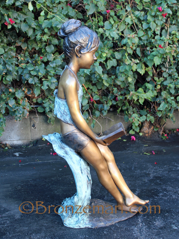 bronze statue of a girl reading