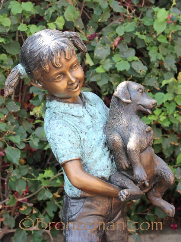 bronze statue of girl with dogs