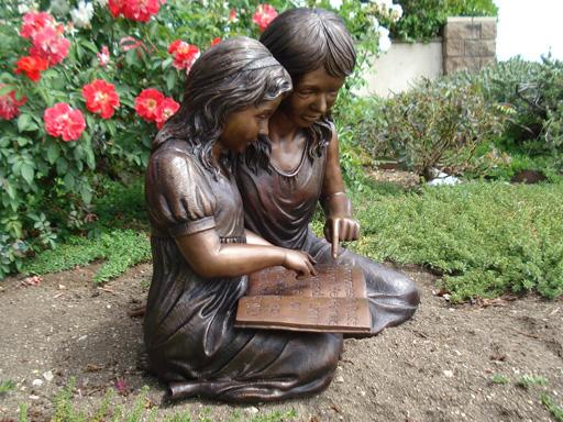 bronze statue of children reading