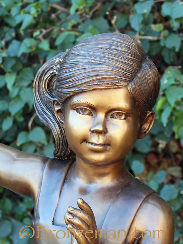 bronze statue of girl in swing