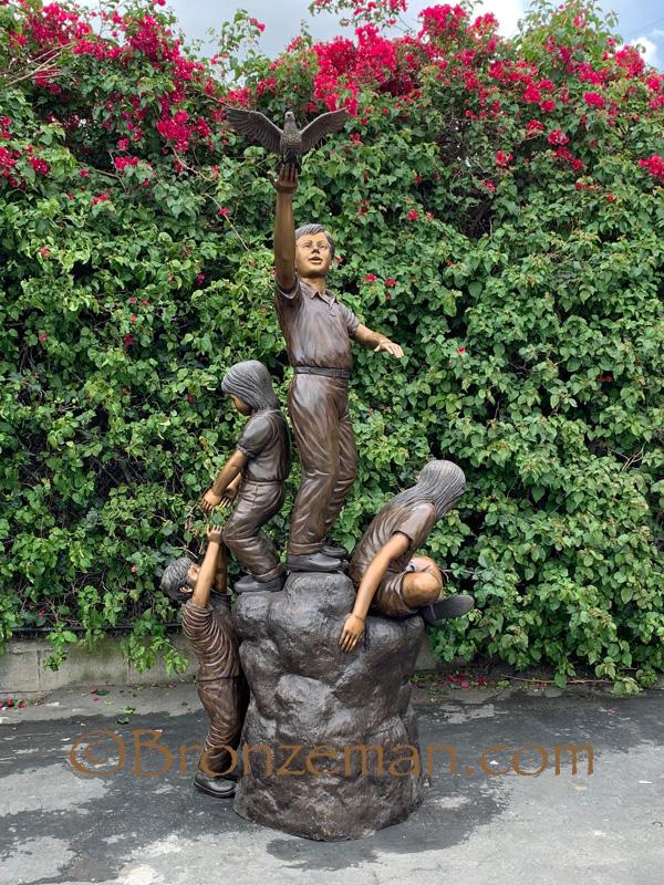 bronze statue of children climbing a rock