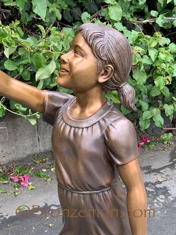bronze statue of boy and girl with flag
