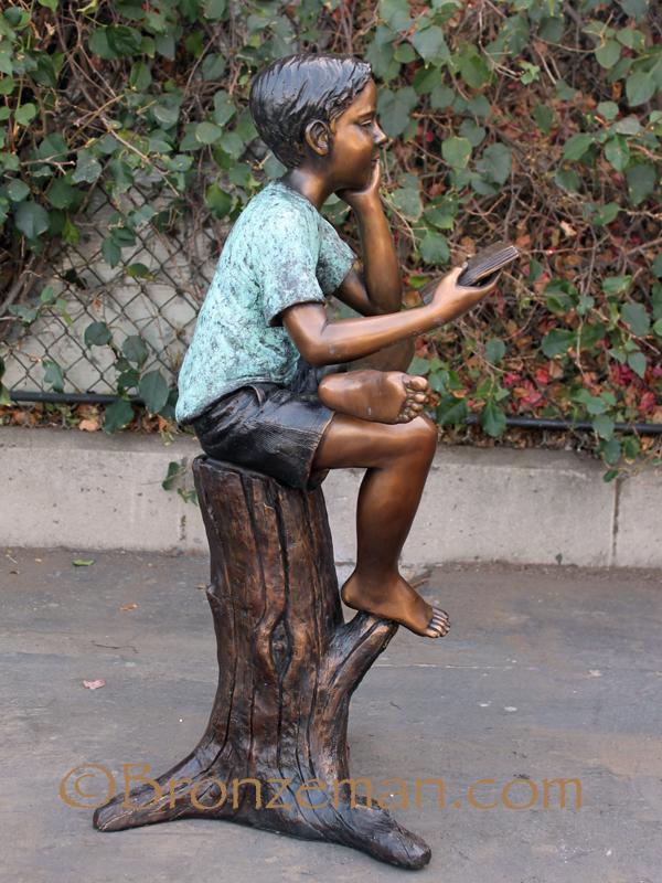 bronze statue of boy reading