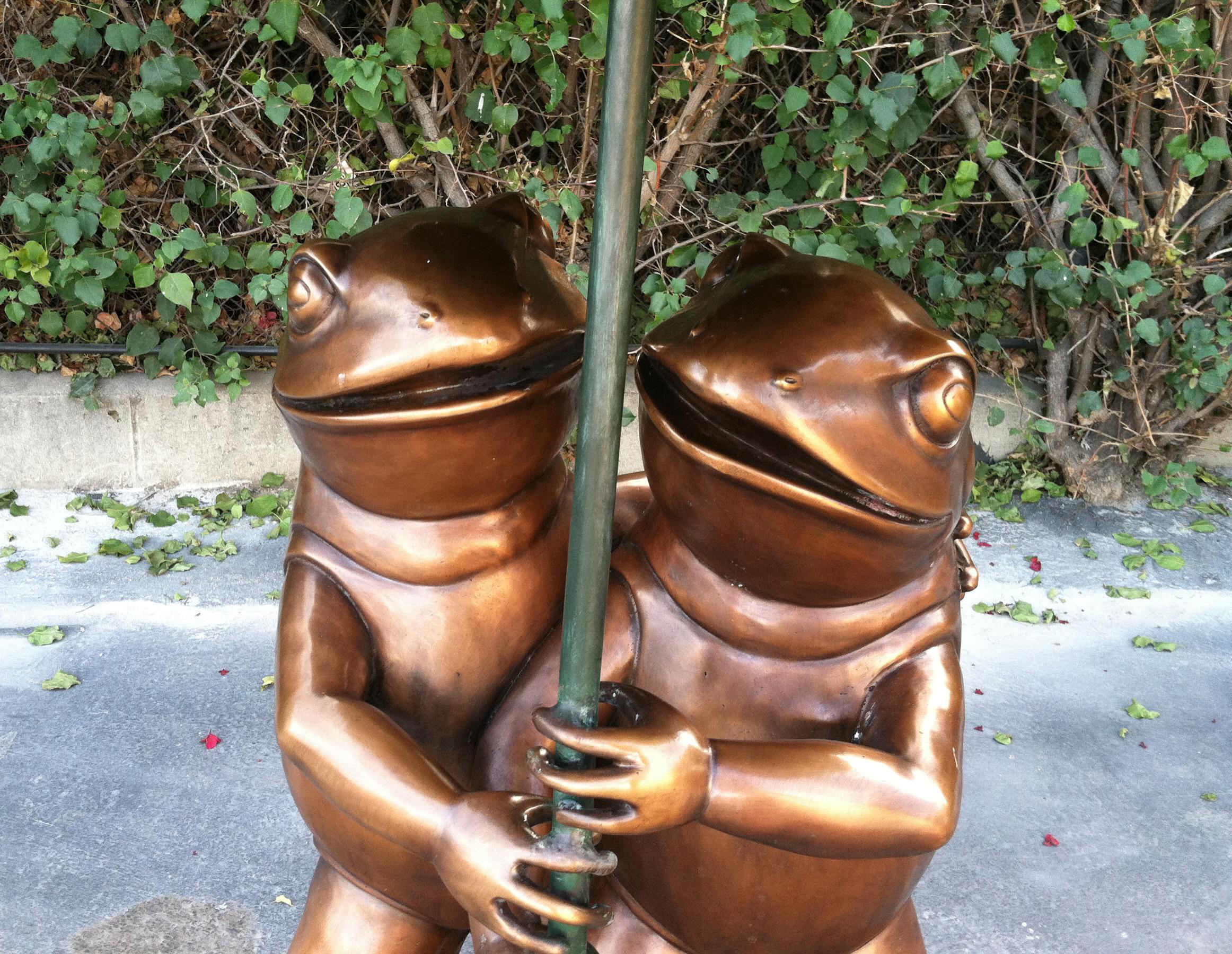 bronze statue of frogs under umbrella