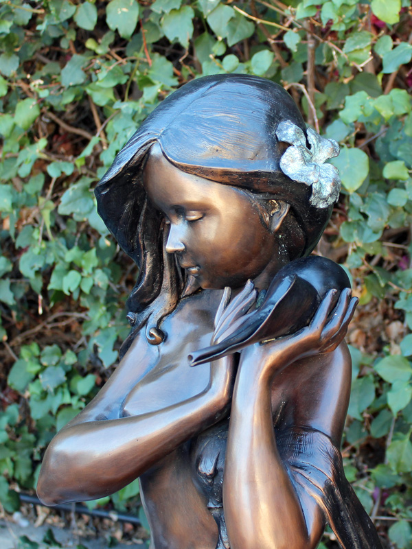 bronze fountain statue of girl holding a shell