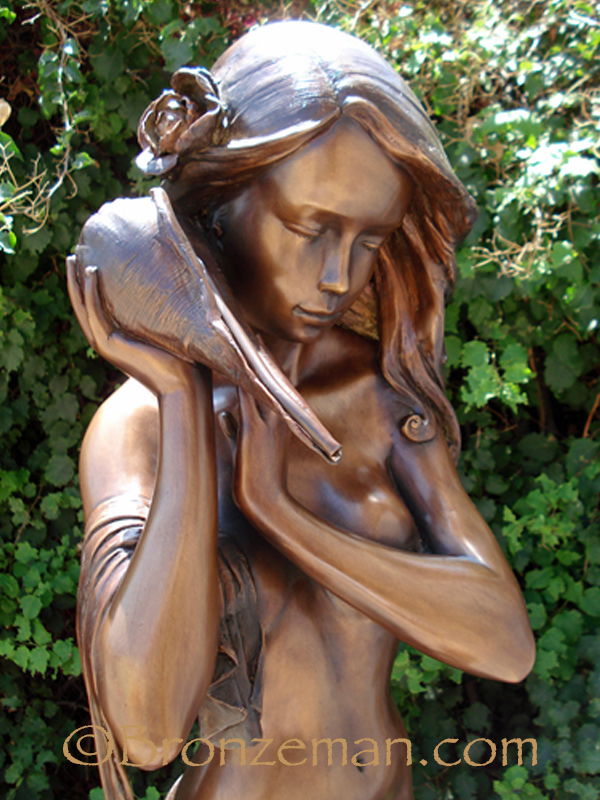 bronze statue of a girl holding shell