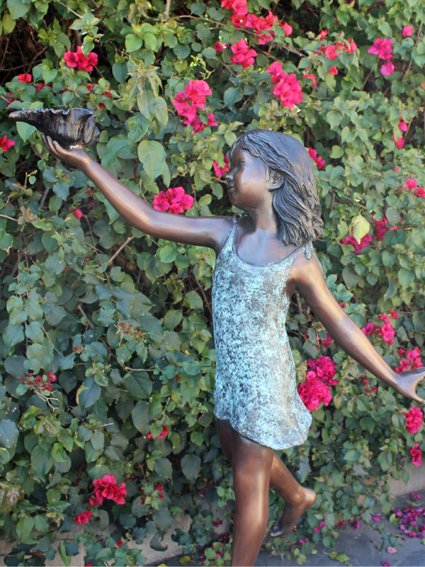bronze statue of a girl standing on a turtle