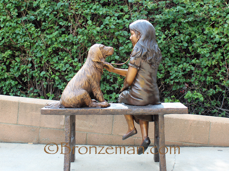 bronze statue of girl with dog on bench