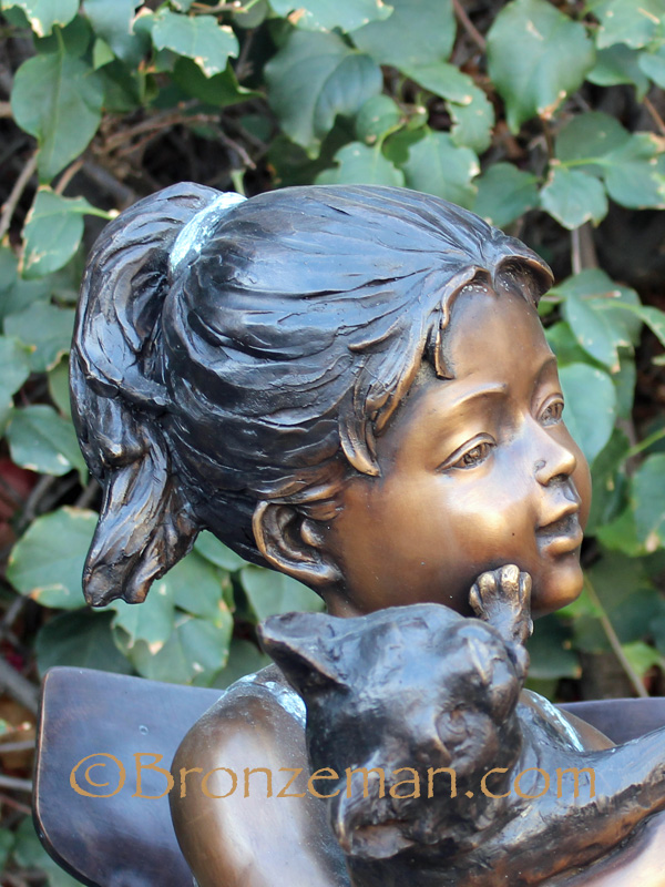 bronze statue of a girl with cat
