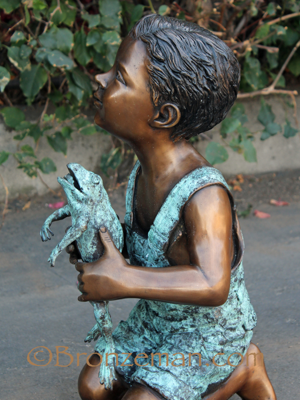 bronze statue of boy with frog