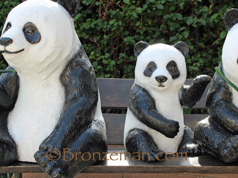 bronze pandas on bench