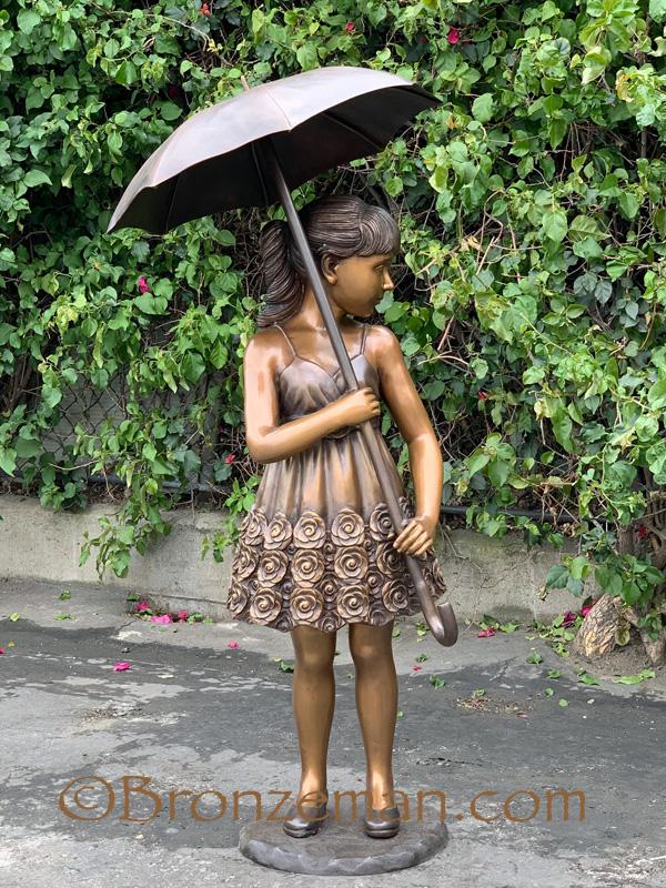 bronze statue of girl with umbrella