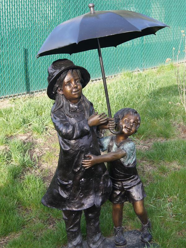 bronze statue of children under an umbrella