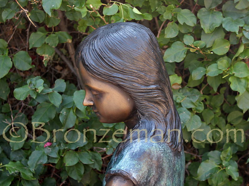 bronze statue of girl with watering can