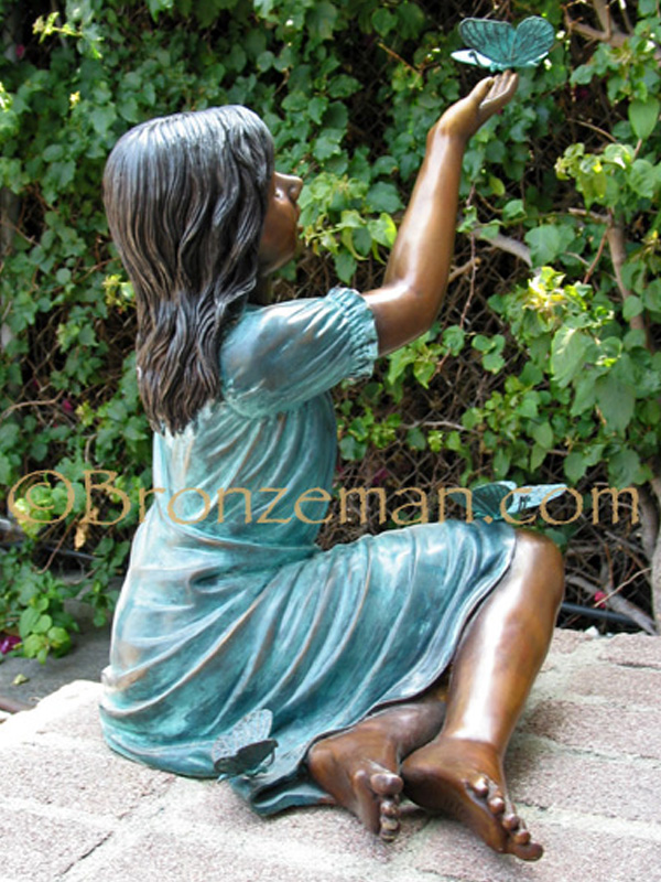 bronze statue of a girl with butterflies
