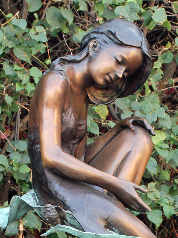 bronze statue of a girl sitting on a leaf