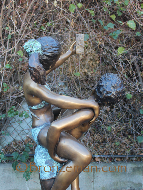 bronze statue of boy and girl taking a selfie